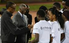 Rwandan President Paul Kagame and former South African president Thabo Mbeki help young people light candles during a night vigil and prayer for genocide victims at the Amahoro stadium in Kigali, Rwanda, on 7 April, 2014. Picture: AFP.