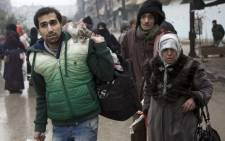FILE: Syrians leave a rebel-held area of Aleppo towards the government-held side during an operation by Syrian government forces to retake the embattled city. Picture: AFP.