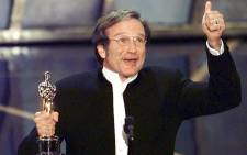 Robin Williams holds up his Oscar after winning in the best actor in a supporting role category for his role as a psychotherapist helping a troubled math genius in 'Good Will Hunting'. Picture: AFP.