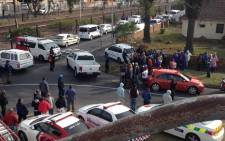 Scores of people, media, police and paramedics stand outside the cordoned off section on the scene where a police officer was shot in the face in Hazendal, in Athlone. Picture: Lauren Isaacs/EWN