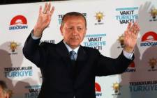 Turkish President Tayyip Erdogan greets supporters at the AKP headquarters in Ankara, Turkey on 25 June 2018. Picture: AFP.