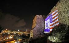 A picture taken on 6 December, 2017 shows a giant US flag screened alongside Israel's national flag by the Jerusalem municipality on the walls of the old city. Picture: AFP
