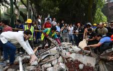 Rescuers look for survivors in a multi-story building flattened by a powerful quake in Mexico City on September 19, 2017. Picture: AFP