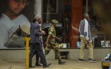 An army officer of the Zimbabwean army walks in Harare's central business district on 15 November 2017. Zimbabwe's military are in control of the country, although generals denied staging a coup. Picture: AFP