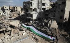 Residents and activists hold a giant a pre-Baath Syrian flag, now used by the Syrian opposition, during an anti-regime protest in the rubble of destroyed buildings in the neighbourhood of Jobar, on the eastern outskirts of the capital Damascus, on 3 March 2016. Picture: AFP.