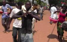 A video grab made on March 24, 2013 shows suspected looters carrying goods as they walk in a street in Bangui on March 24, 2013. Rebels seized control of Bangui and the coup-prone country's president disappeared. Picture: AFP
