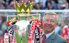 In this file picture taken on May 22, 2011 Manchester United's Scottish manager Sir Alex Ferguson celebrates with the English Premier League trophy after their match against Blackpool at Old Trafford in Manchester, north west England. United celebrated winning the league for a 19th time beating Liverpool's long standing record. Picture: AFP.