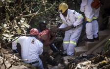 A mine rescue team helps pull an injured illegal miner out of the disused Langlaagte gold mine shaft entrance. Picture: AFP