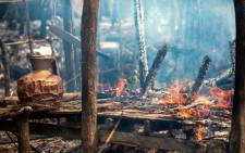 In this photograph taken on September 7, 2017, a smoldering house that was consumed by fire is seen in Gawdu Tharya village near Maungdaw in Rakhine state in northern Myanmar. Picture: AFP..