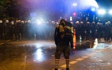 FILE: A man stands in front of police officers as the police clears an anti-G20 protest with a water canon in Hamburg on 5 July, 2017. Picture: AFP