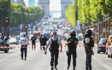 Police officers and anti-riot police officers patrol the Champs-Elysees Avenue on 19 June 2017 in Paris after a car crashed into a police van before bursting into flames, with the driver being armed, probe sources said. Picture: AFP.