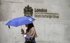 Commuters walk past the London Stock Exchange in the City of London on August 9, 2017. Picture: AFP.