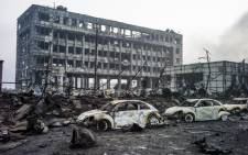 Burnt out Volkswagen cars are pictured amongst the damage on the second morning after a series of explosions at a chemical warehouse hit the city of Tianjin, in northern China on 14 August, 2015. Picture: AFP.