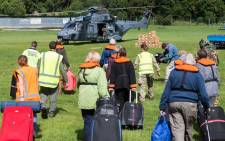 This handout photo from the New Zealand Defence Force taken and received on November 16, 2016 shows people walking to a helicopter with their suitcases as hundreds of tourists are evacuated from Kaikoura Picture: AFP
