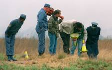 FILE: Members of the South African police force continue their search of a Boksburg field, east of Johannesburg, in September 1995, where the bodies of ten murder women victims were found. Picture: AFP.