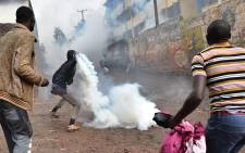 A resident is watched by stone-throwing companions as he prepares to throw back a teargas canister during clashes with Kenyan police officials at Katwekera village within Kibera slum - a stronghold of opposition leader Raila Odinga - in Nairobi on 26 October 2017. Picture: AFP