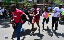 Civil rights activists run to escape teargas as a canister goes-off on the ground during a demonstration on 5 February, 2018 in the streets of Nairobi. Picture: AFP
