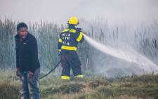 FILE: A man walks past a firefighter putting out a blaze in Masiphumelele. Picture: chrispreenphotography.com.