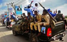 Security forces drive past campaign posters of the forthcoming Somali presidential elections in Mogadishu, Somalia. Picture: AFP.