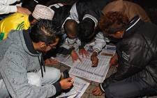 Matric pupils check for their names in the local newspaper, in Johannesburg, on 6 January 2010. Picture:  EWN