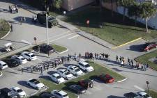 People are brought out of the Marjory Stoneman Douglas High School after a shooting at the school that reportedly killed and injured multiple people on 14 February, 2018 in Parkland, Florida. Picture: AFP.