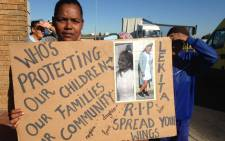 FILE: A community member holds a poster of slain Lekita Moore outside the Bishop Lavis Magistrates Court on Wednesday 14 September 2016. Picture: Lauren Isaacs/EWN.