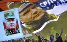 A man waves a flag with a picture of Bosnian Serb war crimes suspect Ratko Mladic during a demonstration in front of Serbian Parliament on 29 May 2011 in Belgrade. Picture: AFP