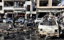 A handout picture made available by Syrian Arab news agency SANA shows Syrian policemen and citizens inspect the site of two terrorist bomb attacks at a security checkpoint in the residential neighbourhood of Zahra, Homs, Syria, 26 January 2016. Picture: EPA/SANA handout.