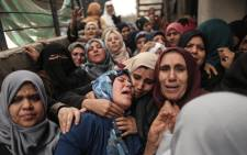 Palestinian relatives of Hamdan Abu Amsha, who was killed by Israeli forces when clashes erupted near the Israeli border, cry during his funeral in Beit Hanun in the northern of Gaza Strip on 31 March 2018. Picture: AFP