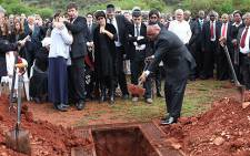 President Jacob Zuma places sand onto former Chief Justice Arthur Chaskalson's coffin during a funeral service at West Park Cemetery. Picture: Taurai Maduna/EWN