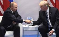 FILE: US President Donald Trump and Russia's President Vladimir Putin shake hands during a meeting on the sidelines of the G20 Summit in Hamburg, Germany on 7 July 2017. Picture: AFP