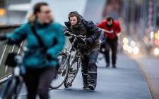 People walk with a bicycle through fierce winds in Rotterdam, on 18 January 2018, during the second western storm of the year. Picture: AFP