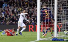 Real Madrid's Portuguese forward Cristiano Ronaldo looks at the ball after scoring a goal during the Spanish league 'Clasico' football match FC Barcelona vs Real Madrid CF at the Camp Nou stadium in Barcelona on 2 April, 2016. Picture: AFP.