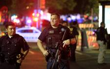 """Dallas police stand watch near the scene where four Dallas police officers were shot and killed on 7 July, 2016 in Dallas, Texas. Picture: AFP."""""""