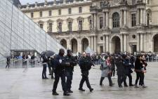"Police officers patrol in front of the Louvre Pyramid in Paris on 4 February, 2017 a day after a machete-wielding attacker lunged at four French soldiers while shouting ""Allahu Akbar"" in a public area that leads to one of the Louvre Museum's entrances. Picture: AFP."