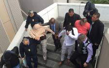 Three City of Cape Town traffic officials are marched out of the Civic Centre after they were arrested for fraud and corruption on 13 July 2015. Picture: Natalie Malgas/EWN
