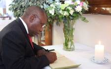 Deputy President Cyril Ramaphosa signs the condolences book at Ahmed Kathrada's home.  Picture: Christa Eybers/EWN