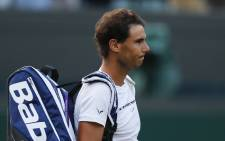 Spain's Rafael Nadal waits for Luxembourg's Gilles Muller to collect his bag so that they can leave the court together after Muller won their men's singles fourth round match on the seventh day of the 2017 Wimbledon Championships at The All England Lawn Tennis Club in Wimbledon, southwest London, on 10 July, 2017. Picture: AFP.