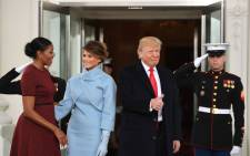 President-elect Donald Trump gives a thumbs up as he and his wife Melania are greeted by US President Barack Obama (not seen) and First Lady Michelle Obama(L) as they arrive at the White House in Washington, DC January 20, 2017.  Picture: AFP