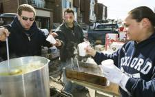 Self-directed volunteers George Kyrtatas (L) and Mike Giletto (C), who own the Sweet Water Bar and Grill in Cinnaminson, New Jersey, serve hot soup on November 6, 2012, from a portable kitchen they drove in to help victims of Hurricane Sandy hit the Oakwood Beach area of Staten Island, New York. Picture: AFP.