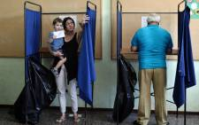 A boy holds his mothers vote as she exits a polling booth during the Greek referendum in Thessaloniki on 5 July, 2015. Greek voters headed to the polls today to vote in a historic, tightly fought referendum on whether to accept worsening austerity in exchange for more bailout funds, in a gamble that could see it crash out of the euro. Picture: AFP.