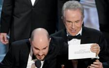 'La La Land' producer Jordan Horowitz (L) holds up the winner card reading actual Best Picture winner 'Moonlight' with actor Warren Beatty onstage during the 89th Annual Academy Awards. Picture: AFP.