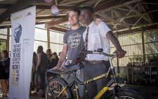 Professional rider Mark Cavendish hands over a bicycle to teenager Siyabulela Lemaoana in Klapmuts on 26 November 2015. Picture: Aletta Harrison/EWN