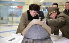 North Korean leader Kim Jong-Un being briefed during an atmospheric re-entry environment simulation of a locally manufactured heat-resistant section of a ballistic missile warhead part at an undisclosed location in North Korea. Picture: AFP.