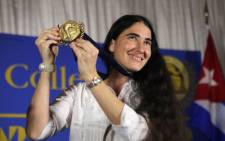 Cuban blogger and independent journalist Yoani Sanchez holds up a Presidential Medal of Miami Dade College given to her during an event at the Miami Dade College's Freedom Tower on 1 April 2013 in Miami, Florida. Picture: AFP