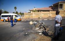 A man stands in front of a barricade after residents of Lombardy East blocked roads in a protest against an informal settlement being erected in their neighbourhood. Picture: Thomas Holder/EWN