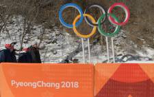 Volunteers walk past the Olympics Rings at the Jeongseon Alpine Centre ahead of the PyeongChang 2018 Winter Olympic Games in Jeongseon on 7 February 2018. Picture: AFP.