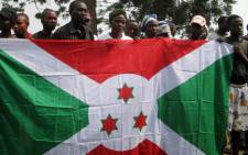 FILE: Burundian refugees who voluntarily came back to Burundi from the Democratic Republic of Congo (DRC) pose with a Burundian flag in the western Burundian town of Gatumba on 5 October 2010. Picture: AFP.
