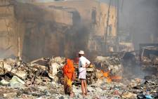 A man and woman look at the damages on the site of the explosion of a truck bomb in the centre of Mogadishu, on October 14, 2017. Picture: AFP