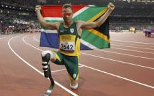 Oscar Pistorius poses with photographs with a national flag after winning gold in the men's 400m - T44 final during the athletics competition at the London 2012 Paralympic Games at the Olympic Stadium in east London on 8 September, 2012. Picture: AFP.